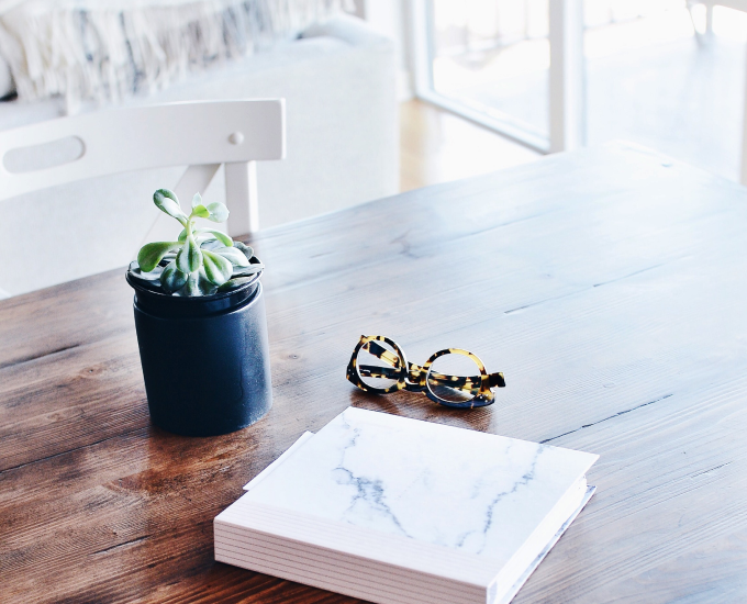 Photo of a plant, book, and glasses on a wood desk